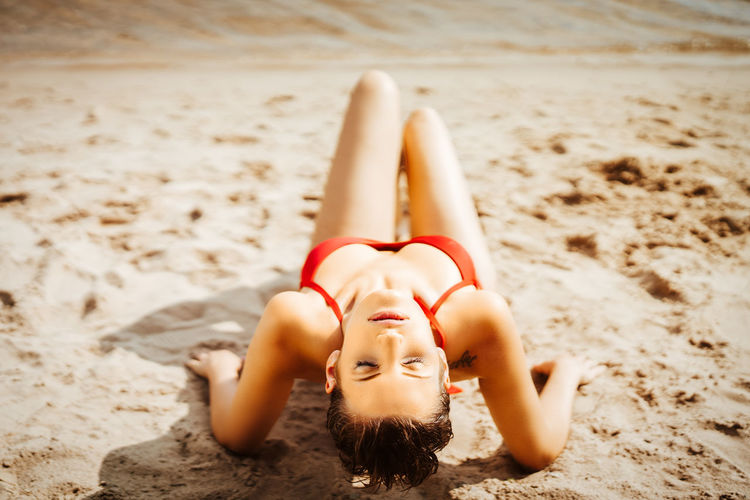 High angle view of sensuous model in bikini posing at beach