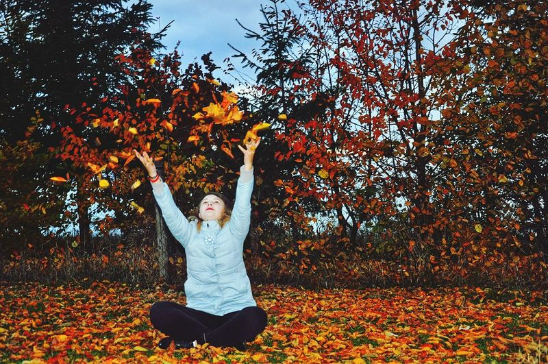 Full Length Of Young Woman Throwing Dry Leaves In Park During Autumn