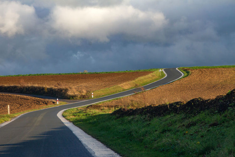 Road Transportation Cloud - Sky Environment Sky Landscape Nature The Way Forward Direction Land Scenics - Nature Field No People Marking Country Non-urban Scene Sign Country Road Rural Scene Road Marking Outdoors Diminishing Perspective Long