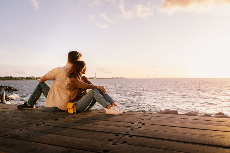 Rear view of couple sitting on sea shore against sky