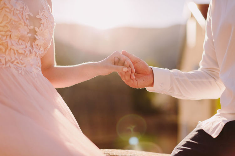 Midsection Of Bride And Groom Holding Hands