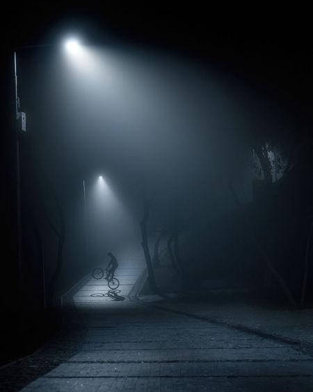 Person on illuminated street at night