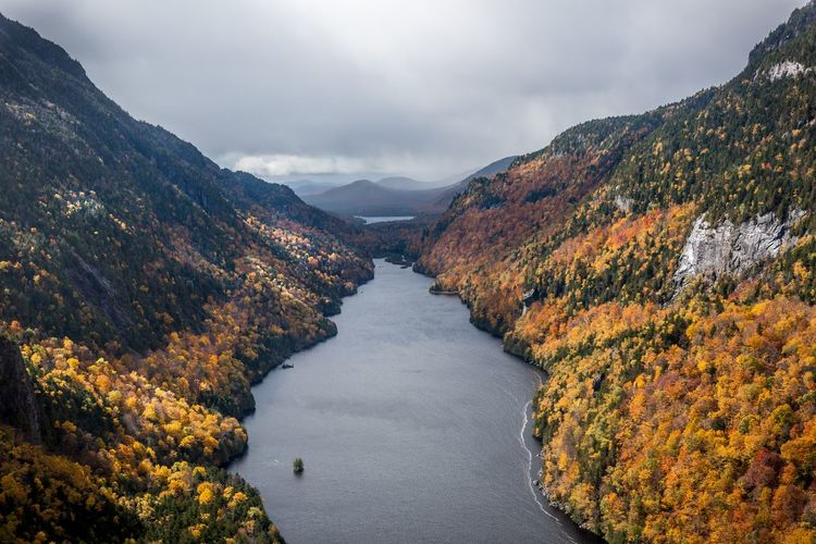 Scenic view of river amidst mountains against sky during autumn