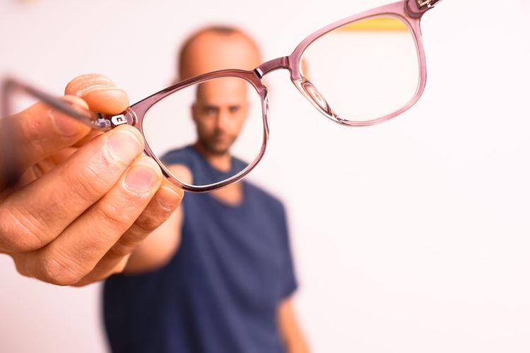 Close-up of man holding eyeglasses against white background