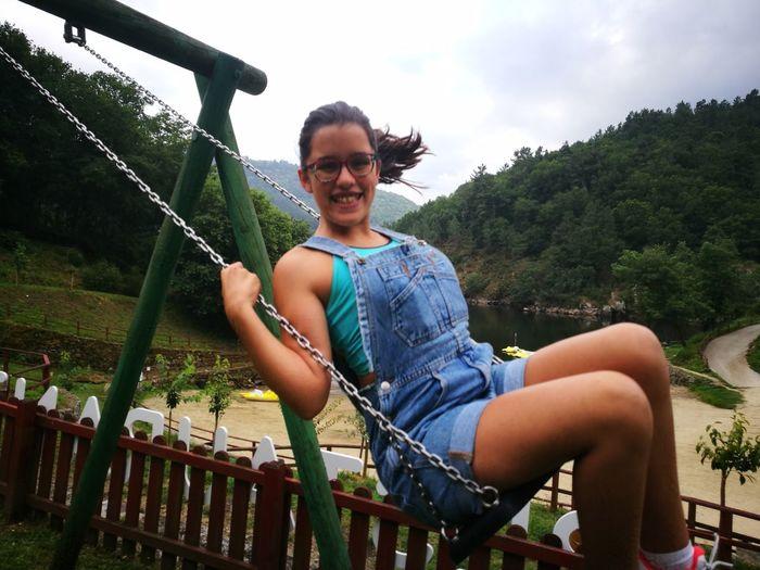 Portrait of smiling teenage girl enjoying on swing