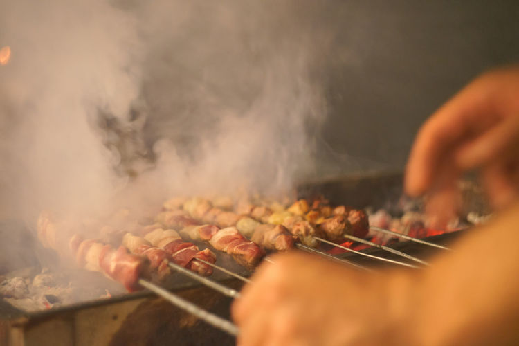 Cropped Hand Grilling Meat On Barbecue