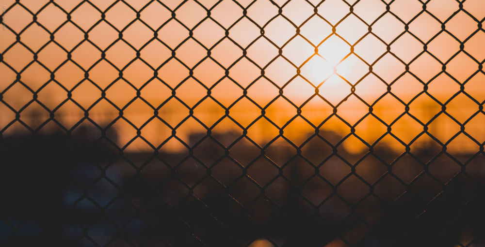 Full frame shot of chainlink fence against sky during sunset