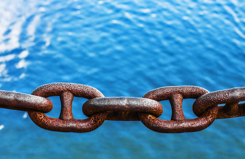 Close-up of rusty chain over sea