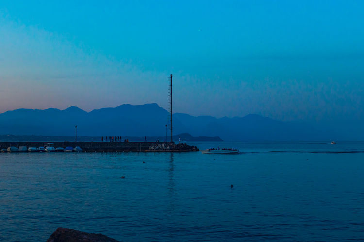 Scenic view of sea against blue sky at dusk