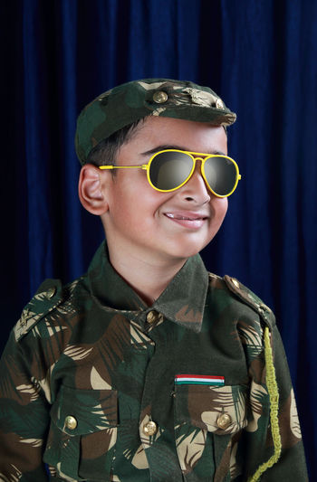 Smiling boy in army uniform and sunglasses standing against curtain
