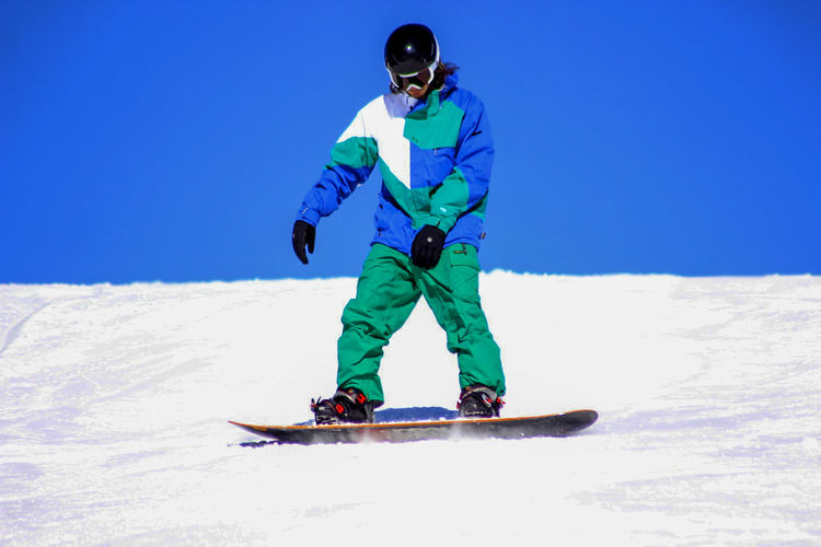 Full Length Of Man Snowboarding On Field Against Clear Sky