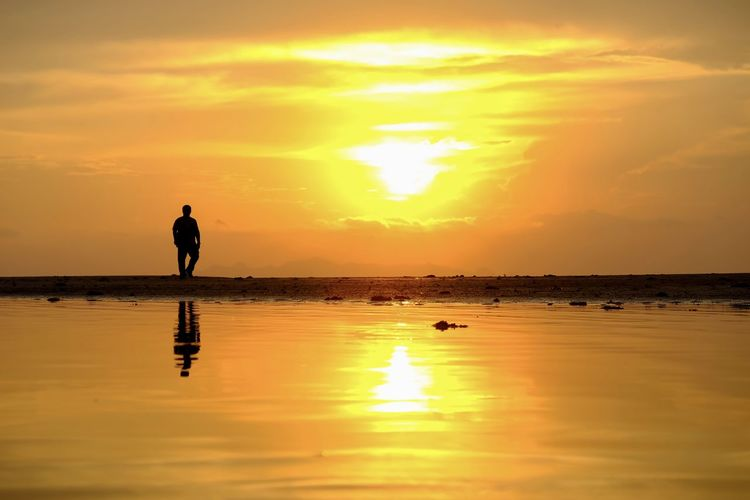 Sunset Sky Water Orange Color Silhouette Beauty In Nature Real People Reflection Cloud - Sky One Person Scenics - Nature Sea Lifestyles Horizon Over Water Horizon Tranquility Standing Leisure Activity Tranquil Scene Sun Outdoors