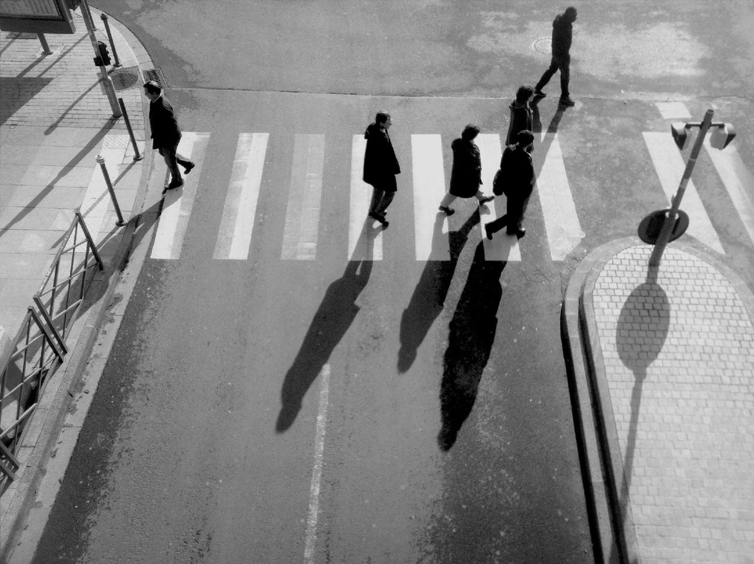men, person, walking, lifestyles, high angle view, large group of people, shadow, street, city life, leisure activity, medium group of people, architecture, built structure, transportation, indoors, day, sunlight, city, in a row