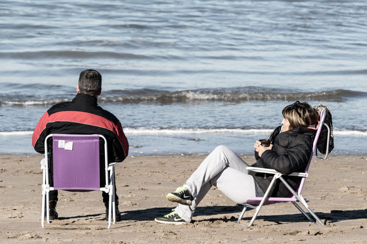 Rear view of men sitting on chair at beach