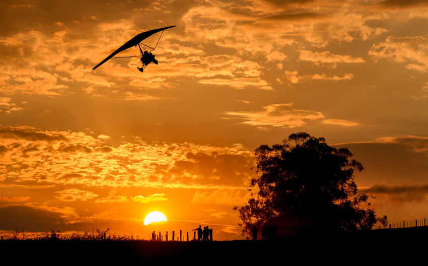 Low angle view of silhouette person hang-gliding against dramatic sky during sunset