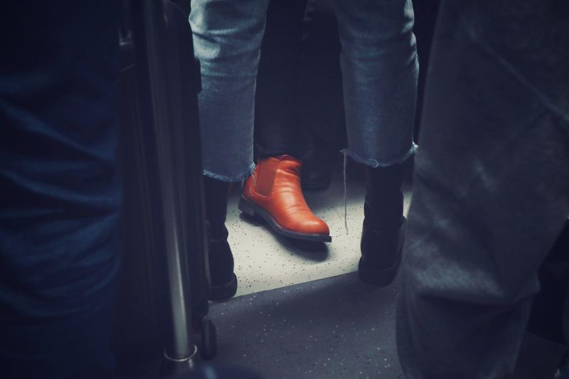 Low section of man wearing shoe sitting in train