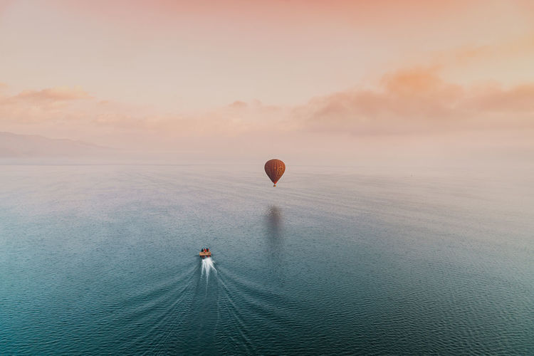 Hot air balloon in sea against sky during sunset