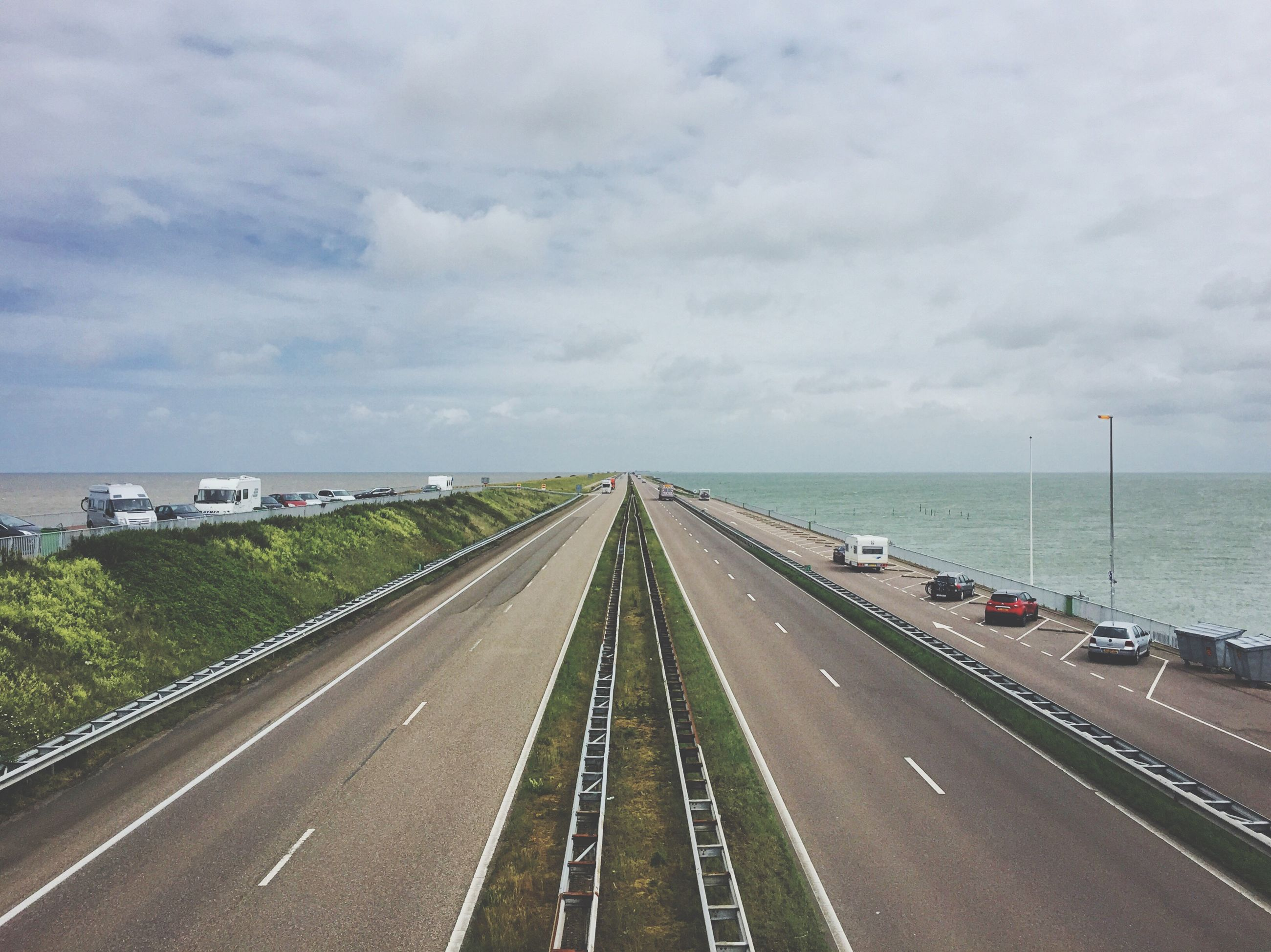 transportation, road, sky, cloud - sky, road marking, mode of transport, diminishing perspective, day, the way forward, land vehicle, car, no people, water, outdoors, sea, nature, scenics, horizon over water, architecture
