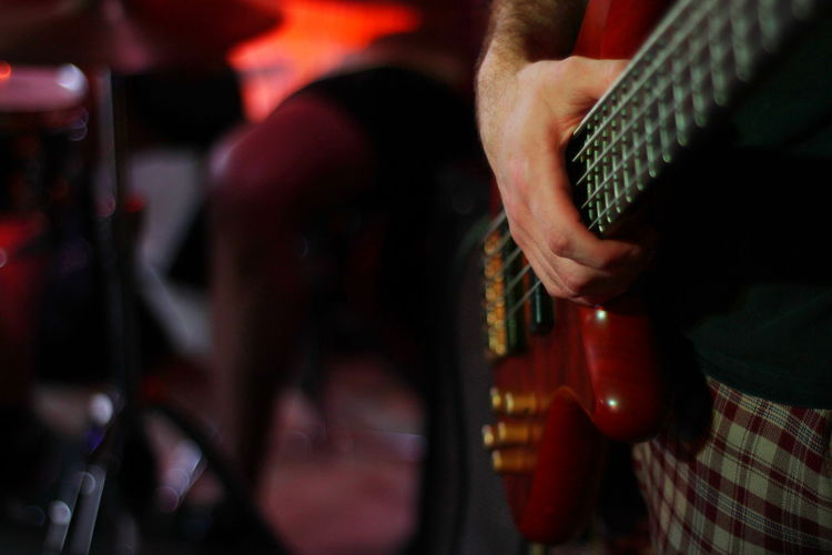 Close up of base guitar on stage Stage Colorful Excitement Fun Night Life Performance Funk On Fire Matches Music Musical Instrument String Instrument Artist Guitar Musician Musical Equipment Arts Culture And Entertainment Guitarist Human Hand Real People Midsection One Person Hand Skill  Plucking An Instrument Playing Men Electric Guitar Rock Music Finger Entertainment Occupation