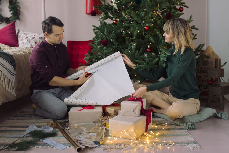 Couple wrapping christmas presents while sitting by tree at home