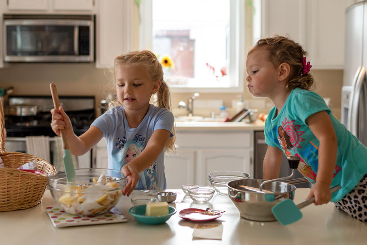 Girl having food in kitchen at home