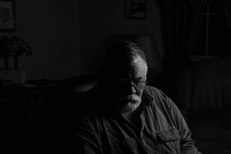 Senior man sitting in dark at home