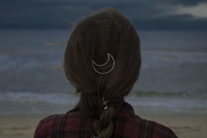 Rear view of woman with moon shape hair clip on hair at beach