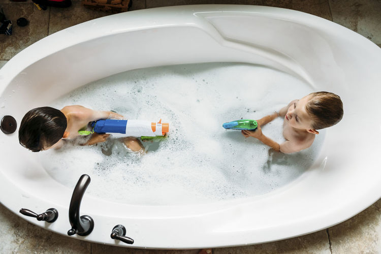 Overhead view of brothers playing with squirt gun in bathtub