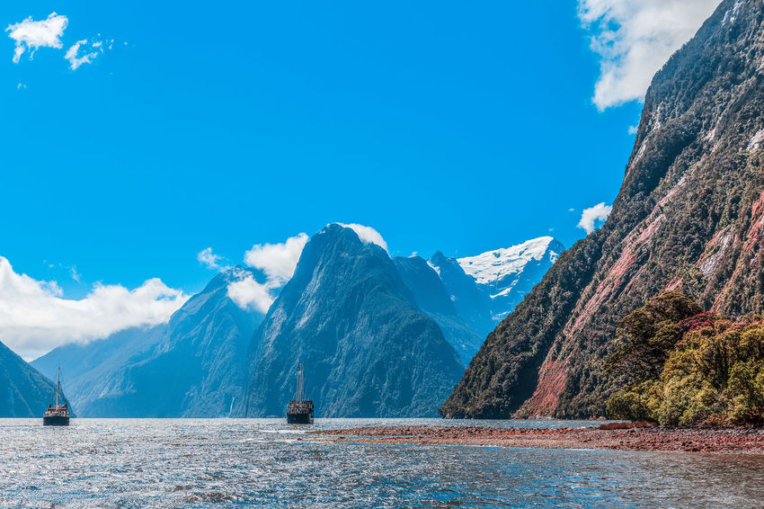 Majestic peaks of Milford Sound with two tourists ships, Fiordland, New Zealand Landscape_Collection Milford Sound Beauty In Nature Blue Cloud - Sky Cold Temperature Day Fiordland Landscape Mountain Mountain Range Nature New Zealand No People Outdoors Range Scenics Sky Snow Snowcapped Mountain Tranquil Scene Tranquility Tree Water Winter