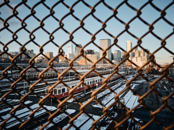 Trains seen through chainlink fence against sky