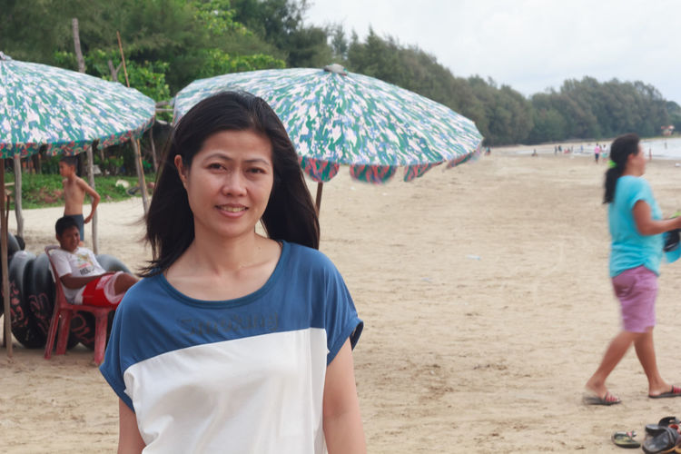 Umbrella Protection Incidental People Real People Security Land Beach Casual Clothing Leisure Activity Lifestyles Group Of People Women People Portrait Adult Day Front View Focus On Foreground Outdoors Rain Hairstyle