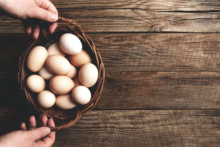 High angle view of person hand holding basked with pasture raised eggs on wooden table background