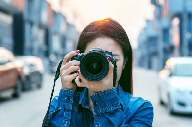 Close-up of woman photographing through camera in city