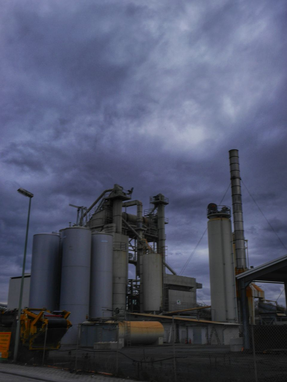 Low Angle View Of Industrial Equipment Against Cloudy Sky At Dusk