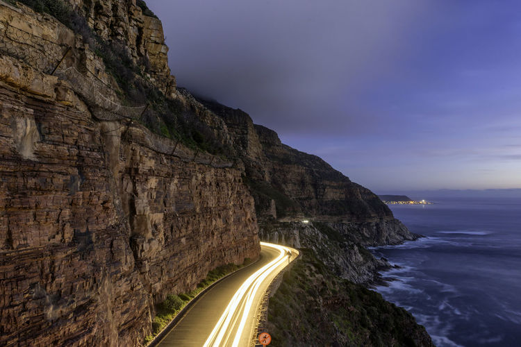 Scenic view of mountain road by the sea