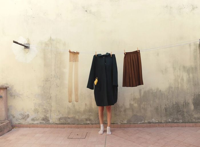 Low section of woman standing by clothes drying against wall