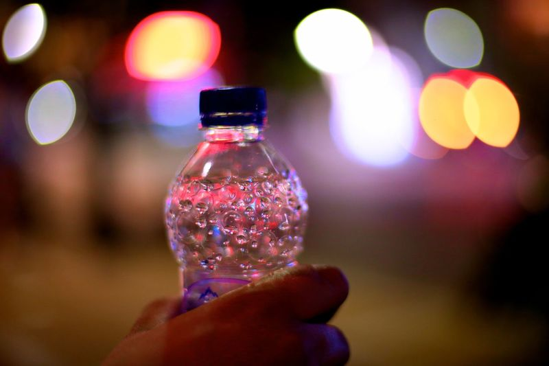 Bokehlicious Nightphotography Reflection Bokeh Bokeh Photography Bottle Bottles Close-up Detail Holding Human Hand Illuminated Light Reflection Light Reflections Multi Colored Night Plastic The Week On EyeEm