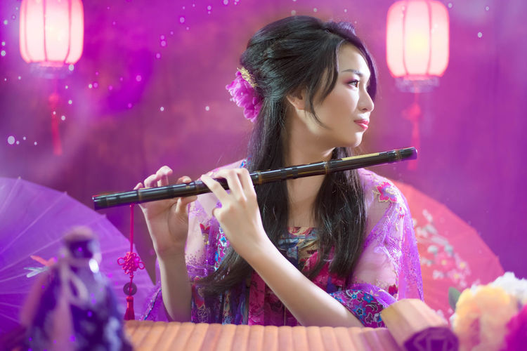 Smiling young woman with flute against illuminated background
