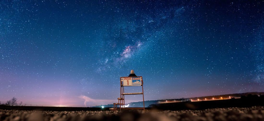 Rear view of person sitting on lifeguard hut at beach against star field