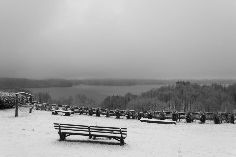 Benches on snow covered field against sky