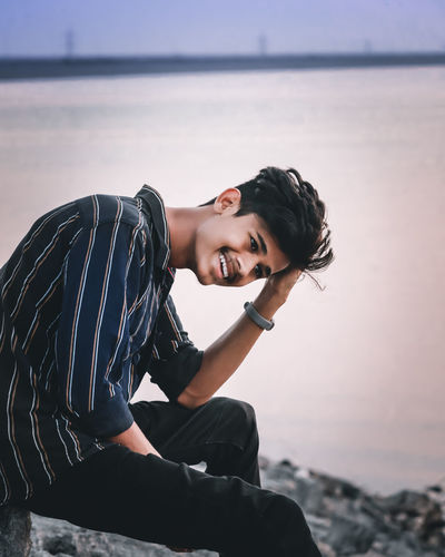 Smiling young man sitting on rock by sea