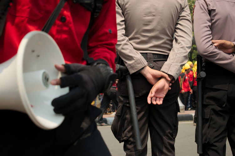 May Day march in Jakarta. Day Flags Human Hand Labor Day March Mayday  Midsection Outdoors Police Police Force Protest Protest Signs Protesters Protesting Real People Red Riots Security Speak Speak Up Technology Uniform The Photojournalist - 2017 EyeEm Awards