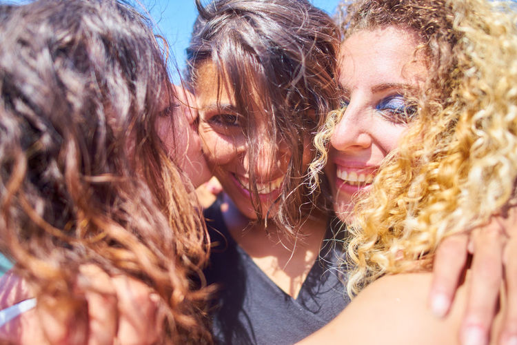Close-up of friends embracing in sunny day