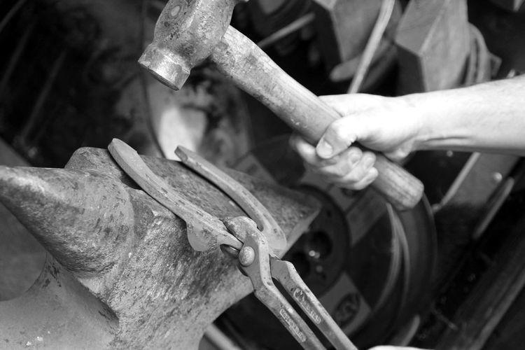 Cropped image of blacksmith hammering horseshoe on anvil