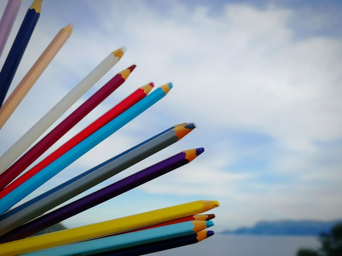 Close-Up Of Colored Pencils Against Sky