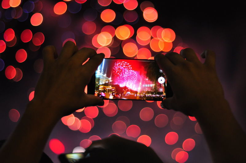 Close-Up Of Person Photographing Fireworks At Night