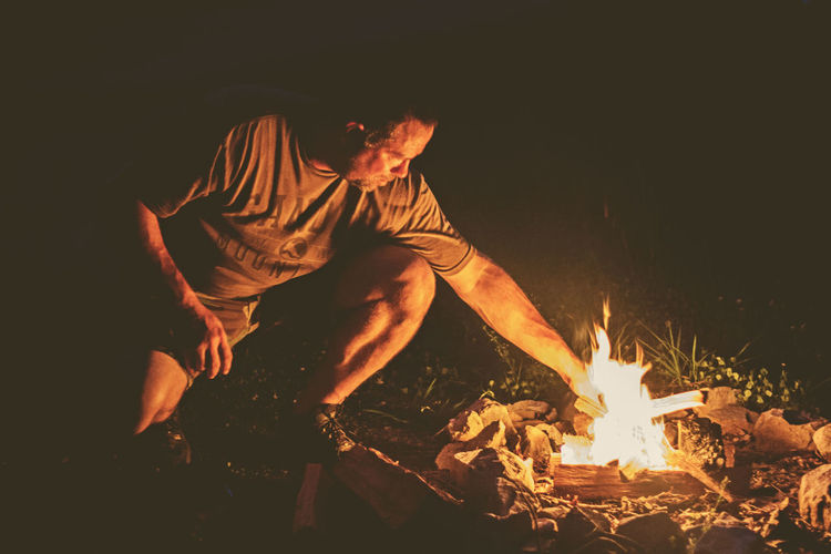 Man Starting a Campfire Burning Campfire Camping Fire Flame Glowing Heat - Temperature Leisure Activity Log Men Night One Person Outdoors Real People Starting A Campgire Starting Campfire Wood
