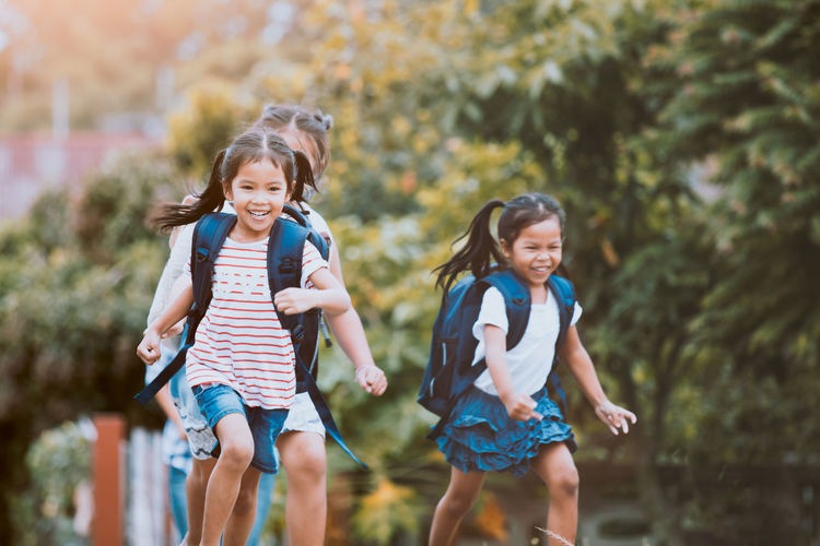 Happy Friends Running With Backpacks Against Plants
