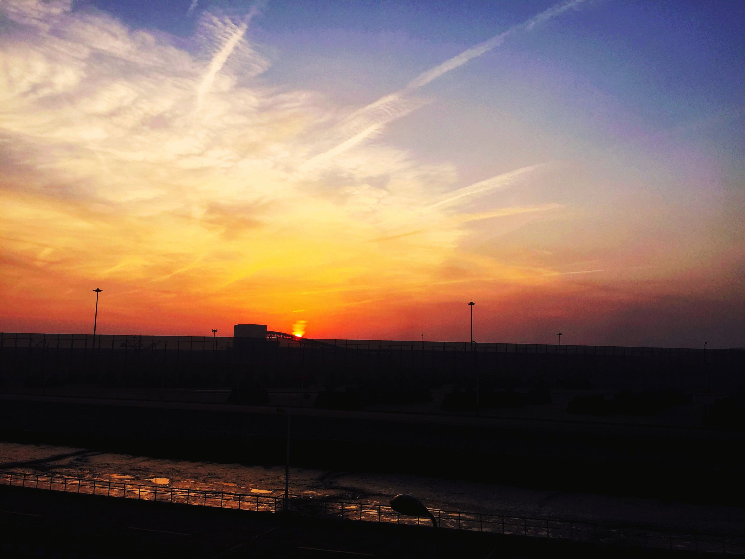 sunset, orange color, silhouette, sky, scenics, beauty in nature, sun, cloud - sky, tranquil scene, tranquility, nature, idyllic, landscape, dramatic sky, cloud, sunlight, outdoors, no people, moody sky, railing