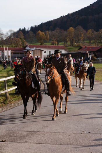 Hundham, Bavaria - November 4, 2017: Every year on the 1st Saturday in November the Idyllic Horse procession, named Leonhardi in the Bavarian Hundham takes place in memory of Patron St. Leonhard. In traditional clothing and decorated horse-drawn carriages horses and riders move to the church of St. Leonhard Bavaria Bavarian Lord God Catholic Hundham Leonhardiritt Leonhardiritt Zur Patron St.Leonhard Saint Leonhard Tradition Domestic Animals Horse Horse Procession Horseback Riding Idyllic Livestock Mammal Men Outdoors People Real People Riding Rural Life Sky Tree Women